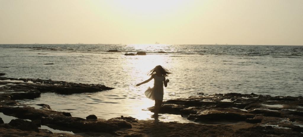 ילדה רוקדת על חוף הים